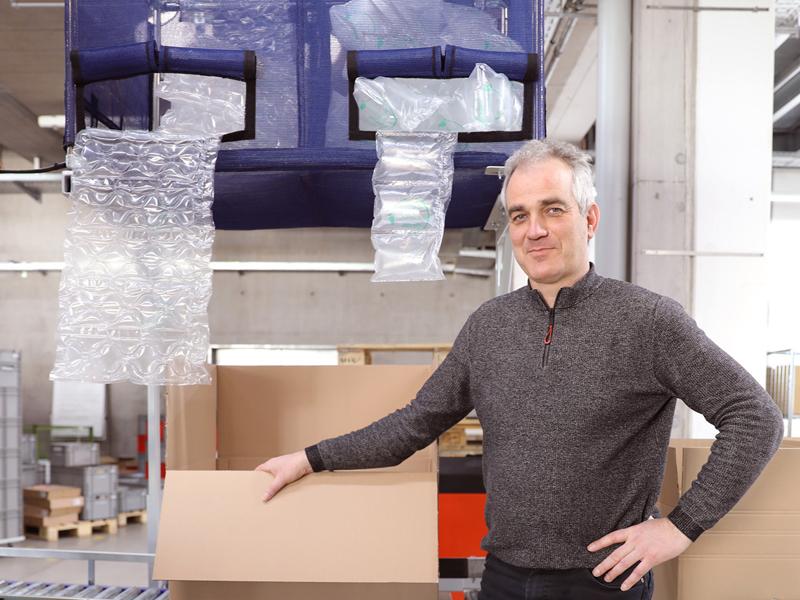 Siedle-Logistikleiter Rainer Broghammer vor den neuen Maschinen zur Befüllung von Luftpolsterkissen.