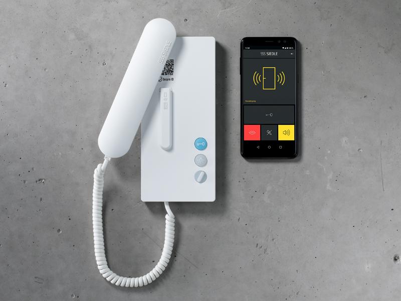 Das IQ-Haustelefon von Siedle bringt den Türruf auch bei älteren Sprechanlagen auf das Smartphone. Der Rat für Formgebung hat die Neuheit mit dem German Innovation Award 2021 prämiert.