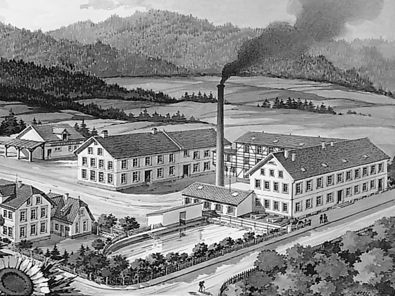 1900: Die Fabrik wächst und erhält eine Dampfmaschine. Links im Vordergrund: das einzige heute noch erhaltene Gebäude.